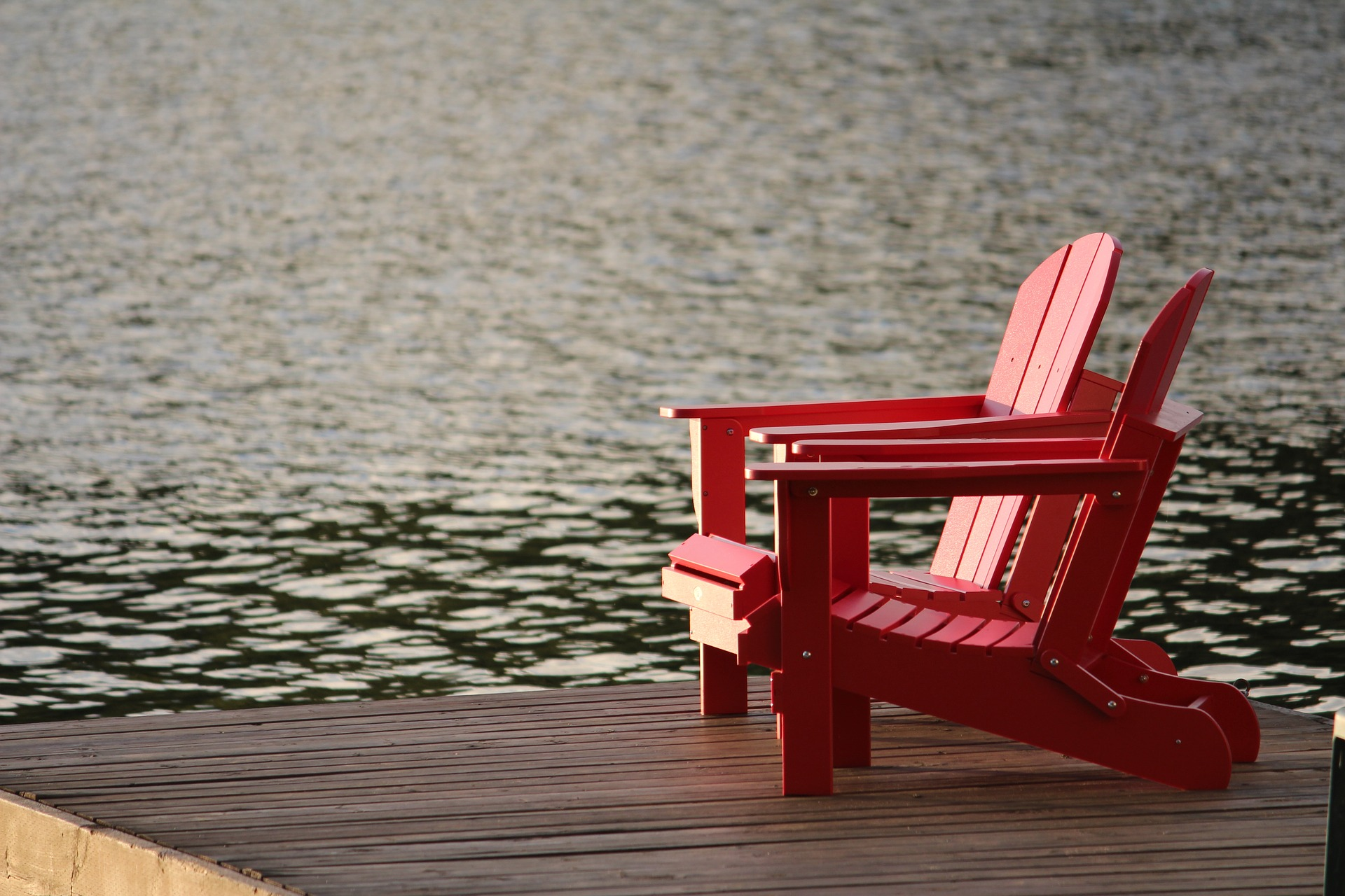 two empty chairs on a dock by the lake giving a retirement feel